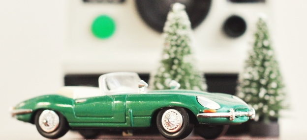 Picture of a toy convertible sportscar in front of toy pine trees dusted with snow